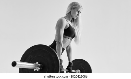 Confident healthy young woman with barbell working out Female athlete exercising with heavy weights at gym Bodybuilder performing deadlift exercise with weight bar Girl crossfit training routine