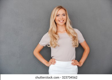 Confident in her abilities. Smiling young blond hair woman holding hands on hips and looking at camera while standing against grey background