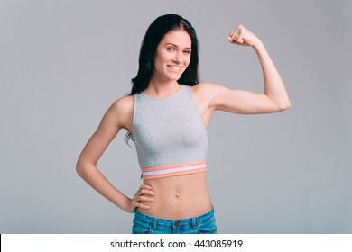 Confident in her body. Attractive young sporty woman showing her bicep and smiling while standing against grey background