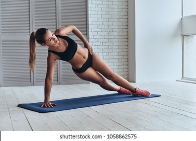 Confident in her fitness regime. Beautiful young woman in sport clothing keeping side plank pose while exercising in the gym