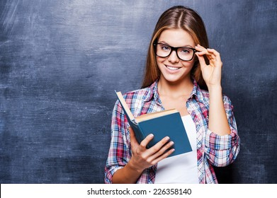 Confident in her knowledge. Cheerful young women holding book and smiling while standing against blackboard