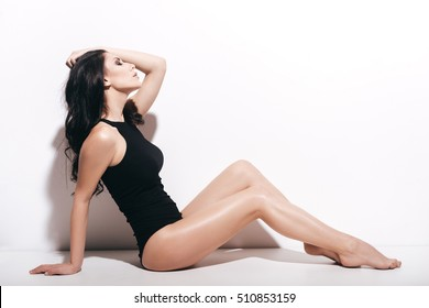 Confident in her perfection. Side view of attractive young woman in black swimsuit holding hand in hair and keeping eyes closed while sitting in front of white background