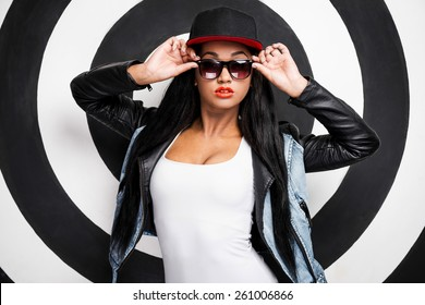Confident in her style. Attractive young African woman in baseball cap adjusting her sunglasses while posing against black and white background