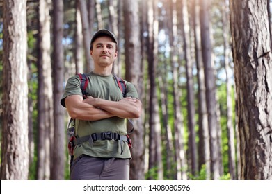 Confident hiker with crossed hands in the forest