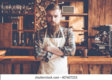 Confident in his new business. Young bearded man in apron looking at camera and keeping arms crossed while standing at bar counter