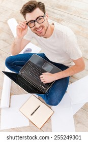 Confident in his new project. Top view of young man working on laptop and looking at camera with smile while sitting on the floor at home