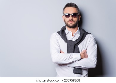 Confident in his perfect look. Handsome young man in sunglasses and smart casual wear keeping arms crossed while standing against grey background