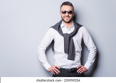 Confident in his perfect style. Handsome young man in smart casual wear and sunglasses looking at camera and smiling while holding hands on hip and standing against grey background