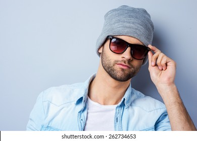 Confident in his perfect style. Handsome young fashionable man adjusting his sunglasses and looking at camera while standing against grey background