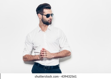 Confident in his style. Stylish young man in white shirt looking away and keeping hands clasped while standing against white background