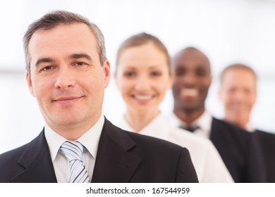 Confident in his team. Confident mature man in formalwear looking at camera and smiling while his colleagues standing in line behind him