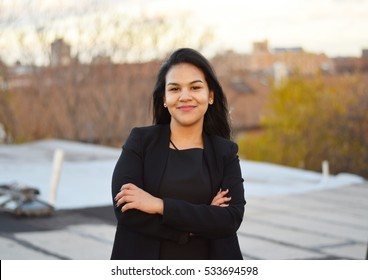 Confident hispanic businesswoman smiling outside with crossed arms