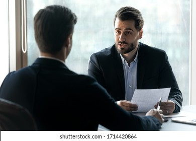Confident hr manager asking questions to candidate on job interview, sitting at desk, holding cv in hands, business partners discussing project strategy, team leader giving instructions to intern