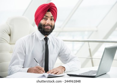Confident indian businessman is working on his computer in the office.