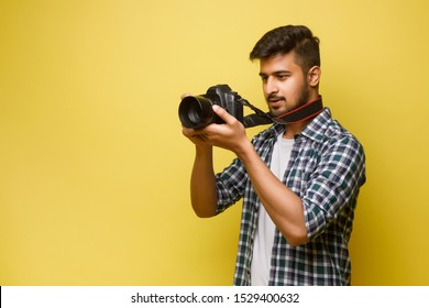 Confident indian man photographer with a large professional camera taking pictures photo shooting on the on the yellow background.