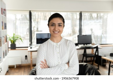 Confident Indian millennial businesswoman posing with hands folded in office. Head shot portrait of happy young female professional, business leader, boss or corporate coach looking at camera.