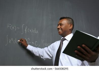 Confident Indian teacher writing math formulas on blackboard