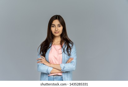 Confident indian young business woman wear blue jeans shirt looking at camera isolated on grey studio background with copy space, pretty hindu female student posing with arms crossed, portrait