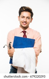 Confident Indian/Asian young Male Doctor with stethoscope and Medical Chart, standing isolated over white background