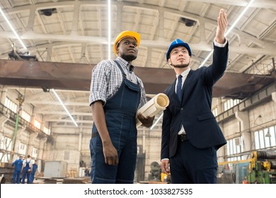 Tour images stock photos vectors shutterstock confident inspector in classical suit pointing at something while young technician with blueprint in hands giving malvernweather Image collections