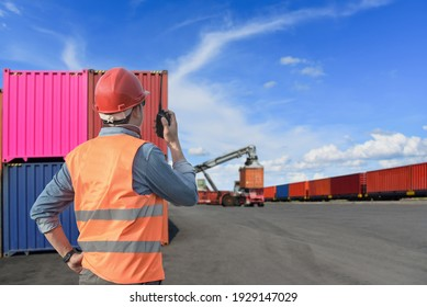 Confident inspector standing in front of cargo container in shipping yard. Smart female engineer, dock worker wear hard hat using clipboard and radio to command transportation. Concept of logistics