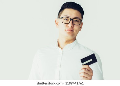 Confident Korean businessman using credit card to pay bills. Serious successful young male entrepreneur in eyeglasses recommending credit card. Cardholder concept