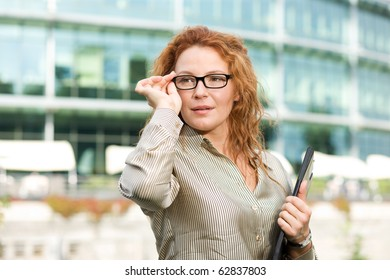 Confident lady in glasses looking away and holding documents in her hands outdoors. Professional manager waiting for new business partners in front of office building.