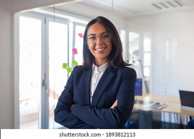 Confident Latin business leader portrait. Young businesswoman in suit and glasses posing with arms folded, looking at camera and smiling. Female leadership concept