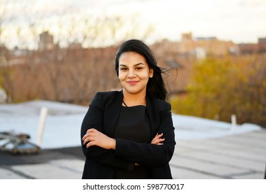 Confident Latina business woman smiling outside (daytime)