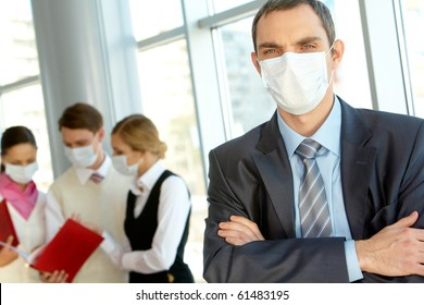 Confident leader in protective mask looking at camera in working environment