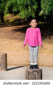 A confident little girl with a pink shirt shows balance by standing on a tree trunk at a park during summer.