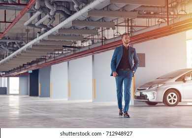 Confident look. Full length of a professional confident businessman walking along the parking lot after having parked his car