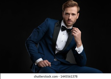 Confident looking groom sitting and leaning on his leg while wearing a blue tuxedo and posing on black studio background