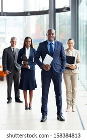 confident male african business leader and team in office