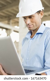 Confident male architect using laptop at construction site