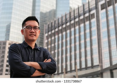Confident male business executive  with arms crossed standing in front of office building background