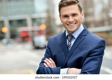 Confident male business executive, arms crossed.