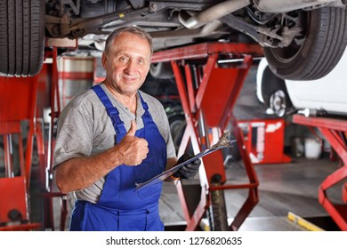 Confident male car mechanic in a workshop writing job sheet for repairs of the vehicle