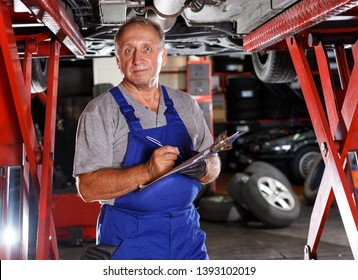 Confident male car mechanic in workshop writing job sheet for repairs of vehicle