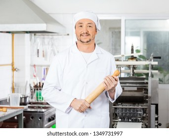 Confident Male Chef Holding Rolling Pin In Kitchen