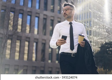 Confident male chief executive of architecture corporation going to meeting with business partners crossing street with coffee to go and chatting with secretary assistant checking preparations