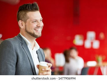 Confident male designer having a coffee at work in red creative office space