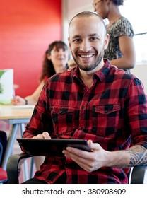Zuversichtliche männliche Designerin, die an einem digitalen Tablet in roten Kreativbüros arbeitet