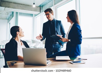 Confident male director communicating with employees controlling productivity of job and talking about tasks,crew of creative female managers having consultancy with proud ceo sitting in loft office