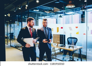 Confident male economist consulting with serious boss while walking near working space in corporation, businessmen in formal suit communicating with each other about project managing in office