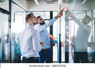 Confident male employee pointing on notes standing with colleague near glass creating infographic for conversation, skilled managers discussing sketches and planning during informal meeting in office
