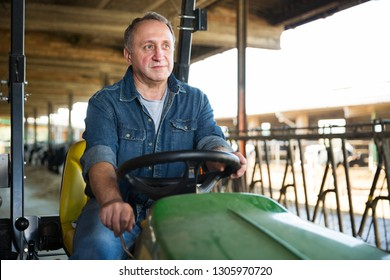 Confident male farm owner driving tractor