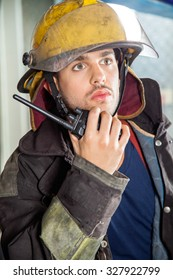 Confident male fireman looking away while using walkie talkie at fire station