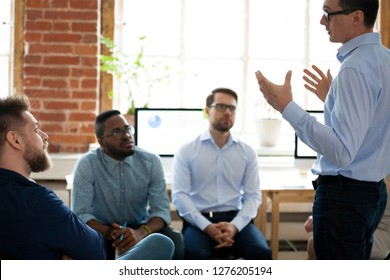 Confident male leader mentor coach speaking at diverse team meeting, presenter speaker manager explaining new business plan strategy to employees group during office briefing at corporate training