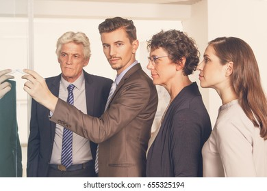 Confident male manager drawing on glassy wall